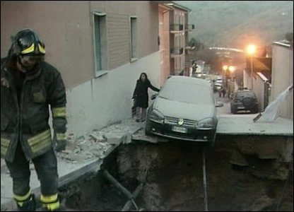 Car hangs over a crater in the road
