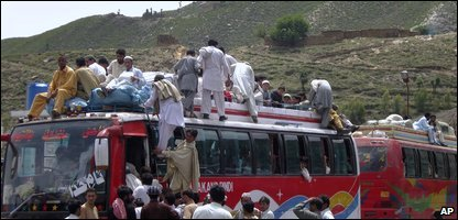 People get onto a bus to leave the north west of Pakistan