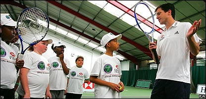 Tim Henman teaches children tennis skills