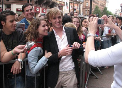 Tom Felton posing for photos with fans