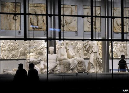 Visitors stand at the Parthenon hall of the New Acropolis museum