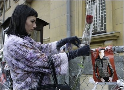 A woman fixes a flower to the fence of the US embassy in Russia.