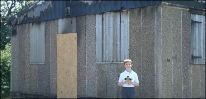 George outside the burnt hut
