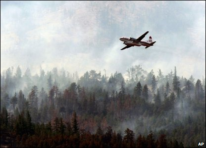 A water bomber flies past a wildfire after dropping fire retardant on the other side of the mountain