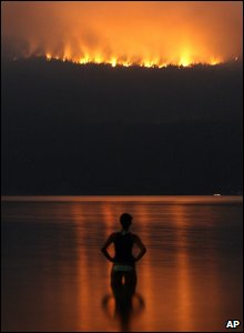 Someone standing in Lake Okanagan watching the wildfires burn on Terrace Mountain