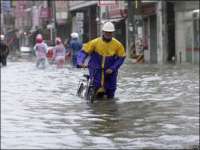This man is attempting to travel through the floods on a bicycle.