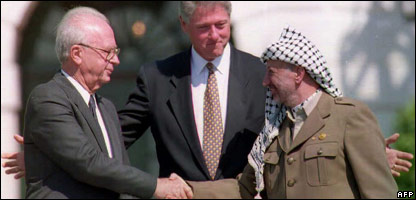 Bill Clinton (centre) standing between Palestine Liberation Organization leader Yasser Arafat (right) as he shakes hands with Israeli Prime Minister Yitzhak Rabin after signing the peace deal in 1993.