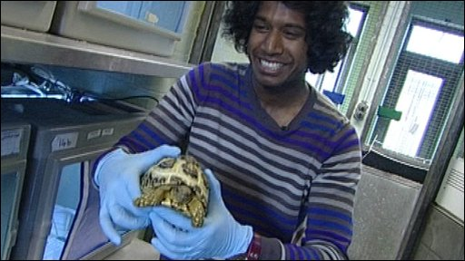 Gavin holding the tortoise as he tries to film a piece of camera