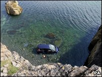 Paige's grandparents' car in the sea at the botto of the cliffs
