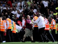 Fans run onto the pitch