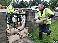 Men place sand bags against gates