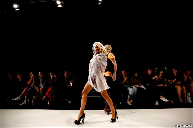 In teetering heels actress Pamela Anderson appears on the catwalk at the