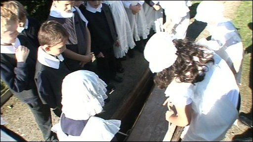 Children take part in a fake funeral