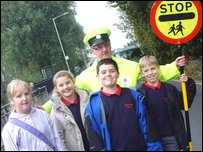 Peter the lollipop man with some of the children he helps across the road