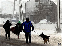 A family walk a dog in the snow near Huddersfield
