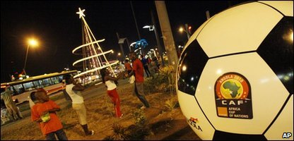 Residents gather next to a giant ball advertising the African Cup of Nations, in Luanda, Angola,