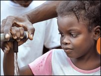 A young girl pumps water