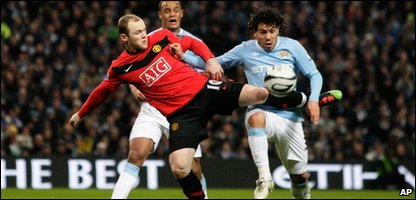 "Manchester City""s Carlos Tevez, right, fights for the abll against Manchester United""s Wayne Rooney during their English League Cup soccer match"