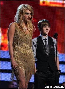 Singers Justin Bieber and Ke$ha speak onstage. Justin's tuxedo was made from recycled materials - his tie was made from old cassette tapes!