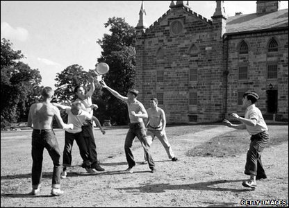 A group of students play catch with a flying disc, likely a pie tin, at Kenyon College, Gambier, Ohio, October 1950
