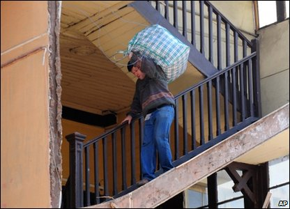 Here a man carries his belongings down the stairs in his apartment block. The outside wall of the building came down in the quake.