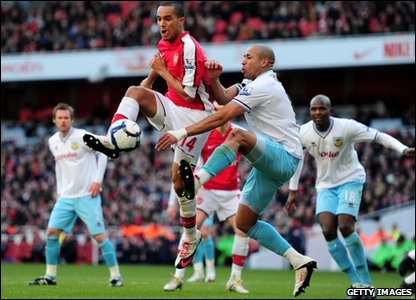 Theo Walcott of Arsenal is challenged by Tyrone Mears of Burnley