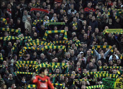 Fans clutch green and gold scarves