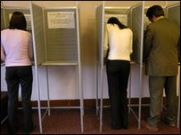 People voting in a booth