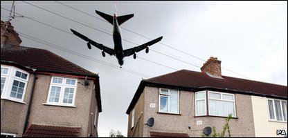 Plane flying over houses