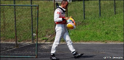 Lewis Hamilton walks back to base after being forced to retire