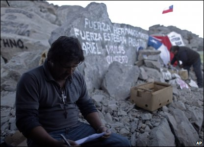 "This is Sandro Rojas Carrizo. His brother Esteban is stuck in the mine. The message on the rocks says: ""Be strong brother miners."""