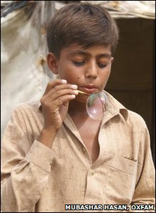 Boy blows bubbles in Pakistan relief shelter