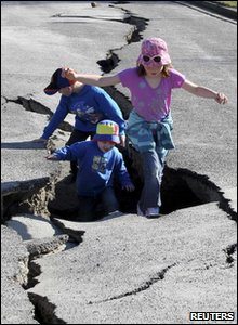 New Zealand earthquake - kids play in crack in the road