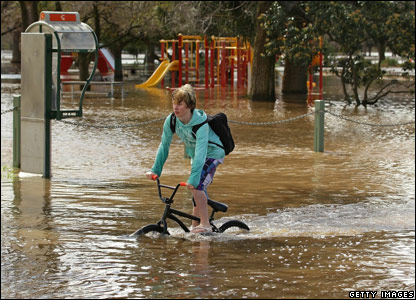 A boy riding his bicycle through floodwater in Benalla, Australia