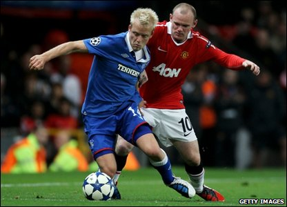 Wayne Rooney of Manchester United tussles for posession with Steven Naismith of Rangers