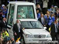 The Pope waves to crowds in Edinburgh from his 'Popemobile'