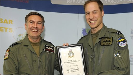 Prince William (R) holds his certificate with Royal Air Force Group Captain Jonathan Dixon