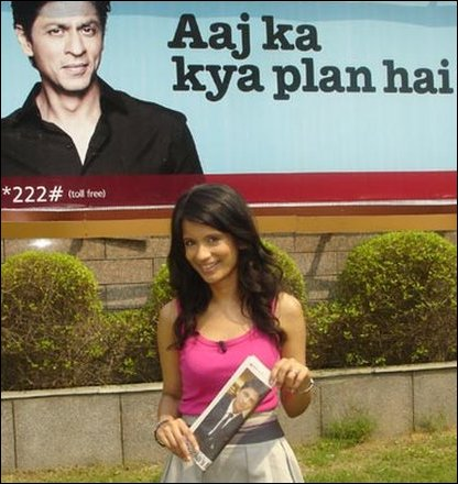 Sonali next to a poster of Bollywood actor Shah Rukh Khan