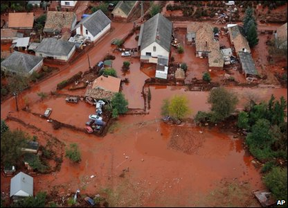 An aerial view of streets covered with red mud and cars piled up by the flood in a yard in Devecser, HUngary