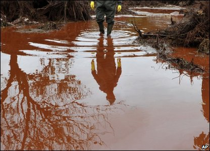 A villager is reflected in a flood of toxic mud, while walking through his backyard in Kolontar, Hungary