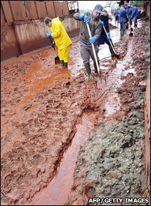Workers cleaning sludge-covered streets in Kolontar, Hungary