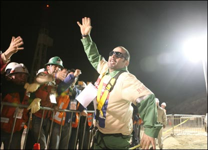 Loads of people are gathered at the mine celebrating as the men are released. Mario Sepulveda shows his happiness!