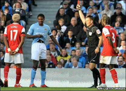 Manchester City defender Dedryck Boyata (second left) is shown the red card by referee Mark Clattenburg during City's match against Arsenal at The City of Manchester stadium