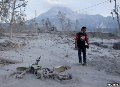 A villager stands in front of Mount Merapi, near his motorcycle covered by ash at Kaliadem village in Sleman, near the ancient city of Yogyakarta
