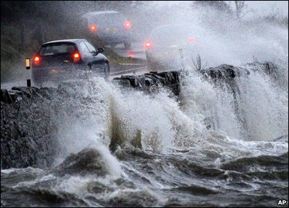 Waves crash onto the road in County Down, Northern Ireland.