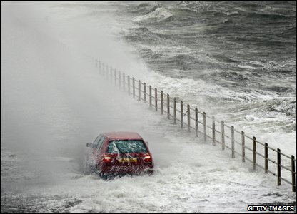 A car covered by waves as it drives along in North Ayrshire, Scotland.