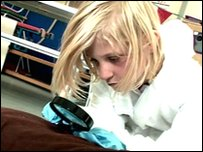 Schoolkid uses magnifying glass to look for clues to solve a (pretend!) murder as part of a science lesson