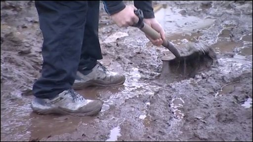 Person clearing mud in the clean-up of flood-hit Cornwall