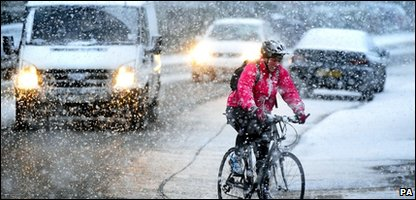 People cycling and driving through the snow in York