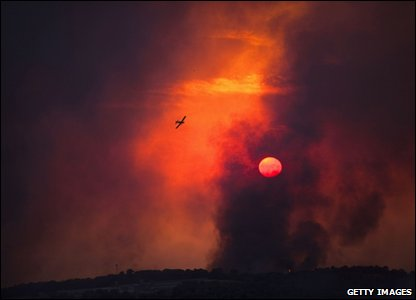A fire-fighting plane flies over a forest fire that broke out in the kibbutz of Beit Oren in the north of Israel